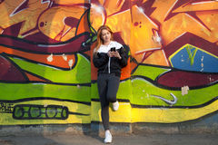 Runner girl resting with mobile phone against bright graffiti wa Royalty Free Stock Photography