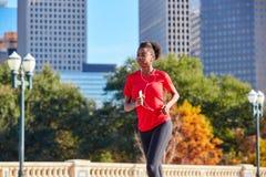 Runner girl running listening music earphones. Runner girl running and listening music earphones in the city park Stock Images