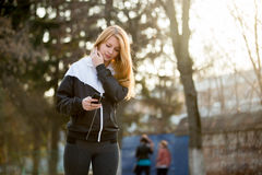 Runner girl with smartphone before morning jogging Stock Photos