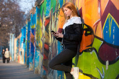 Runner girl with smartphone before morning jogging Stock Image