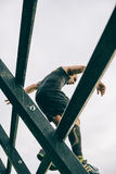 Runner going down wall in a test of extreme obstacle race Stock Photography