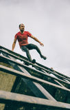 Runner going down wall in a test of extreme obstacle race Royalty Free Stock Photography