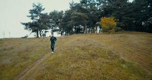 Runner going downhill on a small pathway. Drone flying backwards, zooming out and panning big yellow hill and forest. Runner going downhill on a small pathway stock video