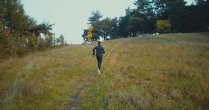 Runner going uphill on a small path to forest. Drone back view. Young endurance athlete running cross country trail. Runner going uphill on a small path to stock footage