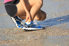 Runner hold her sports injured ankle during sports training on beach Royalty Free Stock Photos