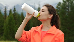 Runner holding bottle of water while resting after evening jog outside, stock footage