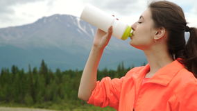 Runner holding bottle of water while resting after evening jog outside, stock video