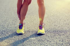 Runner holding her injured leg on road Royalty Free Stock Image