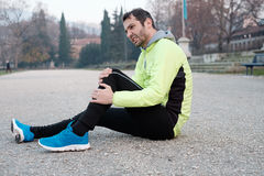 Runner with injured ankle while training. In the city park in cold weather Royalty Free Stock Photo