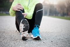 Runner with injured ankle while training in the city. Park in cold weather Stock Image