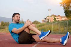 Runner with injured knee on the track Stock Images