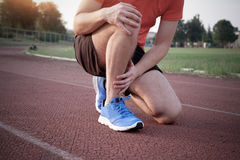 Runner with injured knee on the track Stock Image