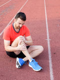 Runner with injured knee on the track Stock Photography