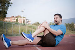 Runner with injured knee on  track Royalty Free Stock Photos