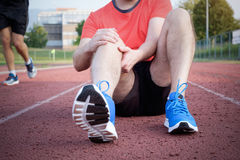 Runner with injured knee on track. Runner with injured knee on the track stock images