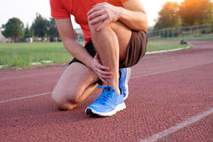 Runner with injured knee on the track Stock Photos