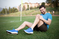 Runner with injured knee on the track Royalty Free Stock Image