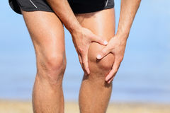 Runner injury - Man running with knee pain. Close-up view of runner injured jogging on the beach clutching his knee in pain. Male fitness athlete Royalty Free Stock Photography