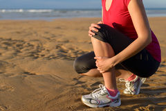 Runner injury shin splint. Female runner clutching her shin because of a running injury and inflammation. Tibial periostitis hurt while jogging on beach stock photos