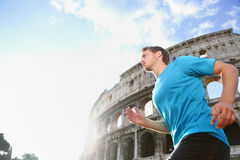 Runner Jogging and Running Against Colosseum. Running male runner jogging against Colosseum. Man athlete on run confident in sportswear. Young man is exercising stock photo