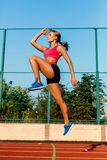 Runner jumping on the jogging track. Woman doing warm-up exercises before running. Royalty Free Stock Photography