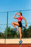 Runner jumping on the jogging track. Woman doing warm-up exercises before running. Stock Photos