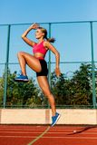 Runner jumping on the jogging track. Woman doing warm-up exercises before running. Stock Image