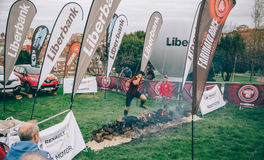Runner jumping over burning logs in a test of extreme obstacle race Stock Image