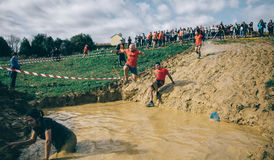 Runner jumping to mud pit in a test of extreme obstacle race Royalty Free Stock Image