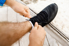 Runner laces his shoes and prepares to jogging. Male runner laces his shoes and prepares to jogging Stock Photo