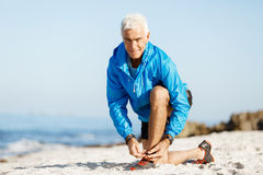 Runner laces his shoes and prepares to jogging Stock Images