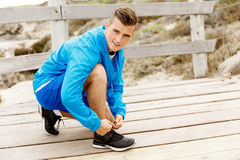 Runner laces his shoes and prepares to jogging Royalty Free Stock Photography