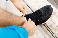 Runner laces his shoes and prepares to jogging. Male runner laces his shoes and prepares to jogging Royalty Free Stock Photos