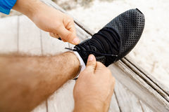Runner laces his shoes and prepares to jogging Stock Photo