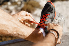 Runner laces his shoes and prepares to jogging Royalty Free Stock Image