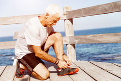 Runner laces his shoes and prepares to jogging. Male runner laces his shoes and prepares to jogging Stock Photography