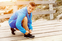 Runner laces his shoes and prepares to jogging. Male runner laces his shoes and prepares to jogging Stock Image
