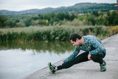 Runner at the lake stretching against green nature Stock Image