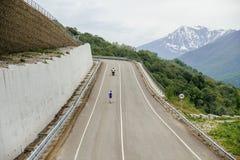 Runner leader of mountain marathon running serpentine asphalt road Stock Photos