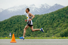 Runner leader race runs in background of mountains and green forests Stock Photo