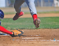 Runner leaps over catchers mitt royalty free stock images