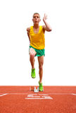 Runner Leaving Starting Block. A young male runner is leaving the starting block in front of a white background. He is looking up and away from the camera and is Royalty Free Stock Image