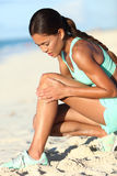 Runner leg injury - Asian running woman with hurting knee pain. Runner injury - running woman upset with hurting knee pain. Asian female athlete with painful Royalty Free Stock Image
