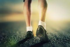 Runner legs on the road at sunrise Stock Photos