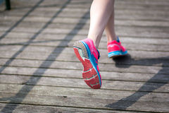Runner legs at wooden bridge. Young women jogging at wooden bridge  . Close-up photo of her legs Royalty Free Stock Images