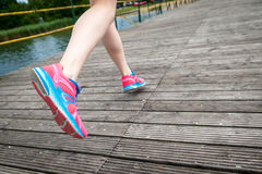 Runner legs at wooden bridge. Young women jogging at wooden bridge  . Close-up photo of her legs Stock Images