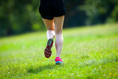 Runner legs. Young women jogging at park . Close-up photo of her legs Stock Images