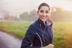 Runner listening music. Young beautiful woman listening music at park while running. Portrait of smiling sporty girl with earphone looking at camera at park in Stock Photos