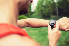 Runner looking checking sport watch Royalty Free Stock Photos