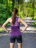 Runner looking at the path through the forest Royalty Free Stock Photography